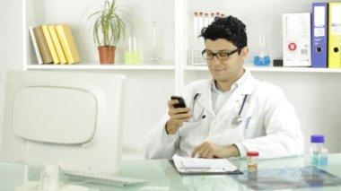 Handsome Young Doctor Texting Smiling Cellphone — Stockvideo
