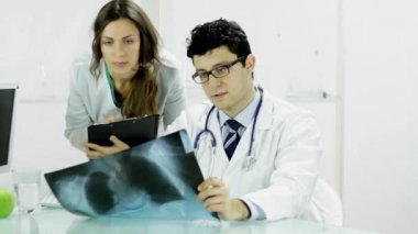 Doctor and Female Nurse Examining X ray in Office — Stock Video