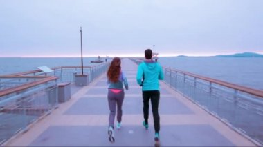 Young Healthy Life Couple Woman Man Jogging On Pier Beach Early Morning Clouds Athletic Lifestyle Sky Blue Uhd 4K — Stock Video