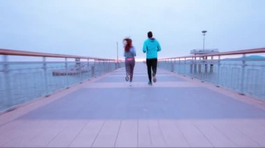 Couple Runners Joggers Running Sea Vacation Pier Early Morning Sunrise Clouds Active Healthy Lifestyle Outdoor Training Workout — Stock Video