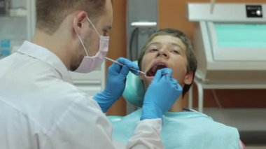 Dentist carry out routine inspection of the patient — Wideo stockowe