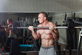 Man practicing with barbell in gym — Stock Photo