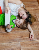 Mom and son playing with tablet pc while lying on the floor — Stock Photo