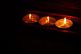 Burning candles on dark background with warm light — Stock Photo