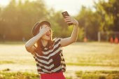 Lovely girl in a hat on the street makes Selfei — Stock Photo