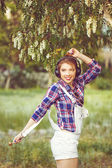 Hipster girl with headphones dancing on the street. — Stock Photo