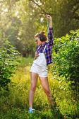 Hipster girl with headphones and cell phone in park dancing. — Stock Photo