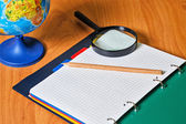 Globe, notebook, pencil and magnifying glass on desk. — Stock Photo