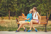 Best girlfriends are reading book while sitting on bench. — Stock Photo