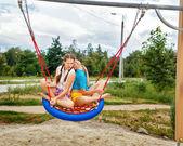 Best friends ride on a swing. — Stock Photo