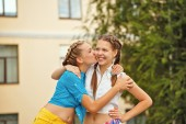 Best friends kiss on the cheek in park. — Stock Photo