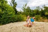 Best girlfriends sitting on sand at beach. — Stock Photo