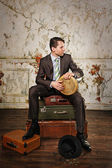 Businessman sitting on suitcases and playing bongos. Collect alm — Stock Photo