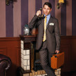Businessman giving instructions over the phone, holding a suitca — Stock Photo #79954434