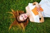 Девушка с книгой, лежа на лужайке. — Стоковое фото
