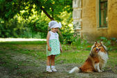 Little girl and dog for a walk. — Stock Photo