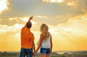 Loving couple looking at the sky at sunset. — Stock Photo