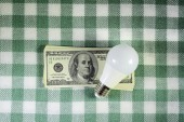 Led light bulb lying on the stack of dollars — Stock Photo