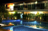 Resort with swimming pool at night — ストック写真
