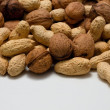 Heap of walnuts and peanuts on white board — Stock Photo #62547077