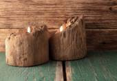 Two candles placed in very old wooden bars on green board — Stock Photo
