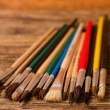 Color paintbrushes on vertical photo placed on wooden board — Stock Photo #64393191
