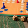 Two wooden dices in front of ludo with figurines — Stock Photo #69485231