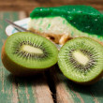 Kiwi fruit sliced in half in front of fresh cake — Stock Photo #70082973