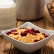 Modern square bowl with cornflakes in front of glass of milk — Stock Photo #73479845