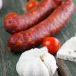 Whole garlic head in front of two sausages — Stock Photo #74646183
