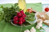 Fresh just harvested bunch of radishes on green towel — Stock Photo