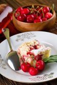 Three cherries in front of pie on white plate — Stock Photo