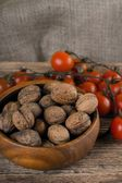 Wooden bowl full of walnuts and branch of tomatoes — Stock Photo