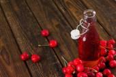 Opened glass bottle with fruit lemonade among several cherries — Stock Photo