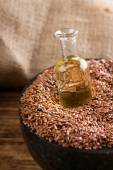 Bottle with flax oil in seeds — Stock Photo