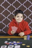 A young boy playing poker at a table — Stock Photo