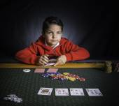 A young boy playing poker at a table — Foto de Stock