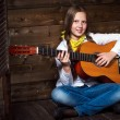 Cute teenager cowgirl plays the guitar — Stock Photo #59910531