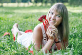 Young woman lying on the grass in the park — Stock Photo