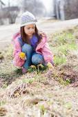 Little girl picking bunch of small yellow flowers — Stock Photo