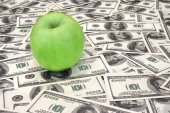 Green apple on heap of dollars — Stock Photo