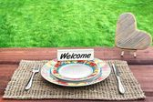 Picnic Table with Wooden Heart and Sign Welcome — Stock Photo