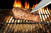 Chef Knife in the Grilled Meat Chop. Flame in Background. — Stock Photo