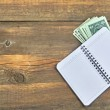 Open Notebook and Money Bills On Grunge Wood Background — Stock Photo #70458911