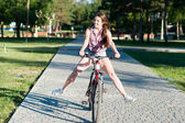 Smiling girl riding on bicycle — Stock Photo