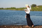 Woman with fan on the coast — Stock Photo
