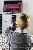 Child watches TV, remote control TV — Stock Photo