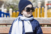 Boy on the street in  mother's sunglasses — Stock Photo