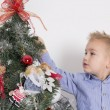 Little boy decorating a Christmas tree — Stock Photo #58510441