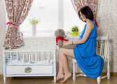 Pregnant woman sitting near the cot — Stock Photo